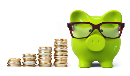 Green piggy bank with glasses and coin stacks in ascending order