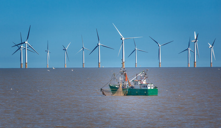 Off sure wind turbine and fishing boat