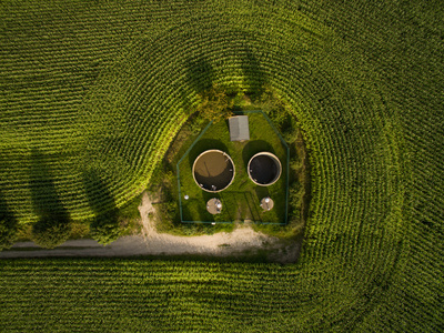 aerial view of small sewage treatment plant betwenn corn plants fields - top view