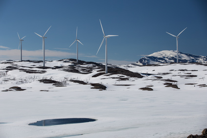Wind turbines on a snowy hill against clear blue sky in Swedish Lapland