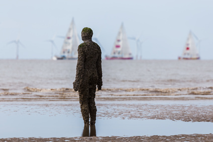An Iron Man watches the start of the 2017/18 round the world Clipper race on a beach near Liverpool. The Clipper Race (now in its eleventh year) sees twelve global teams compete in a 40000 nautical mile around the world race on a 70 foot ocean racing yachts. The teams left the host port of Liverpool on 20 August 2017 to begin their first leg – a 5200 mile mile journey lasting approximately 33 days to South America, taking in the Canary Islands & Doldrums along the way.