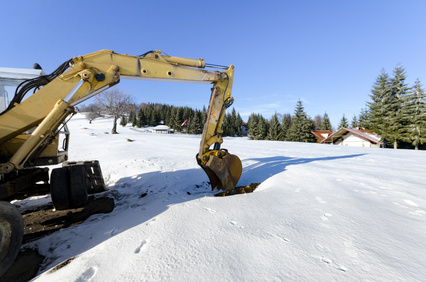 Industrial excavator loading soil material at winter snow construction site