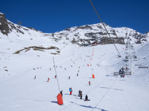 people skiing on a ski slope full of snow in a clear winter day . chair lift on the right
