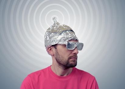 Bearded funny man in a cap of aluminum foil sends signals