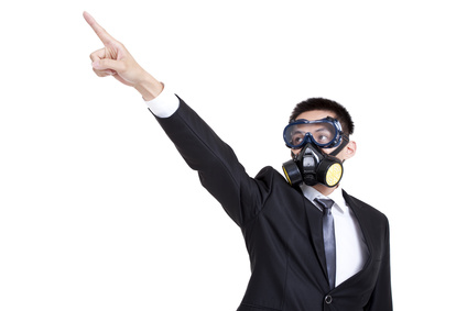 Young businessman with gas mask pointing afar