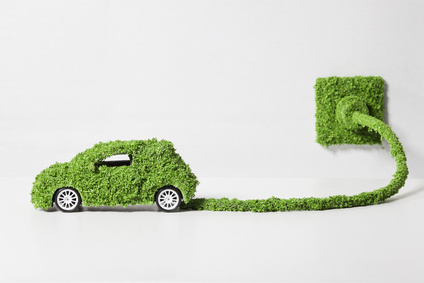 Electric car covered with grass connected to socket, close up