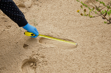 Expert measuring the shoe print length in the desert