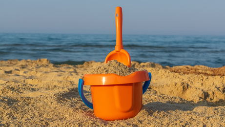 A bucket and shovel in the sand of a beach ,closeup, copy space. Beach and holiday concept.