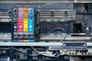 Old, dirty, disassembled inkjet printer. View of internal parts. Closeup.