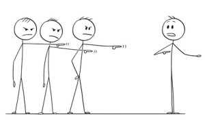 Cartoon stick drawing conceptual illustration of team of businessmen or coworkers or colleagues blaming one of them. Business concept of failure and responsibility.